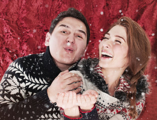 Happy young couple playing with snow
