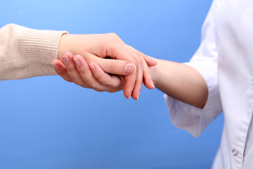 Medical doctor holding hand of patient, on light background