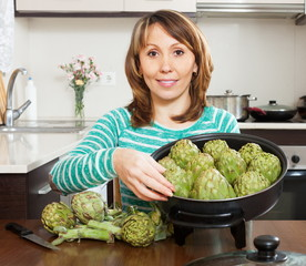 Woman cooking artichoke in pan