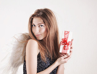 Portrait of young woman as angel with little gift for Valentine'