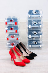 Shoes in plastic boxes and female shoes on floor in room
