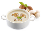 Mushroom soup in white bowl, on plate, isolated on white