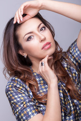 Brunette model on grey background with hands above the head
