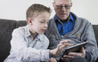 Boy showing old man how tablet computer works