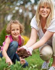 Mutter und Tochter pflanzen Blumen im Garten