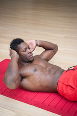 Young black african man portrait exercising abdominal muscles at