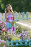 Watering, flower garden - beautiful girl watering roses with gar