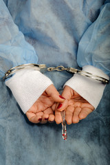 Criminal handcuffed medical person with bloody lancet in hand