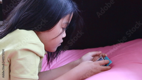 young lady play mobile games on the bed