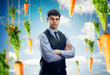 Businessman against blue sky with red carrots  around