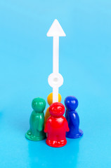Growth concept. Group of the toy people and arrow pointing up