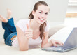 Attractive young woman using laptop showing thumbs up