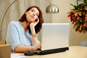 Pensive woman sitting on her workplace at home