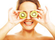 woman holding kiwi fruit for her eyes.