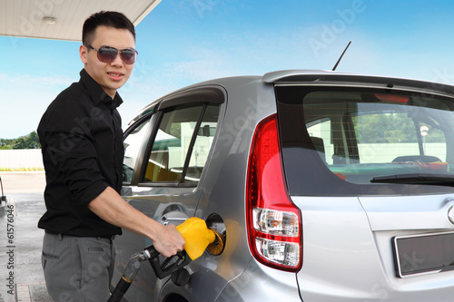 A young man refueling his car
