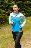 Sportive woman running  through meadow