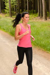 Sportive woman running through forest