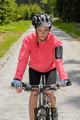 Woman riding mountain bike sunny countryside path