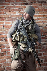 Portrait fo soldier with rifle on bricks background