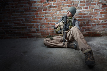 Soldier with rifle on bricks background