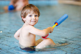 Activities on the pool, toddler boy swimming, having fun and pla