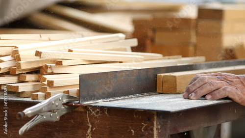 carpenter cutting wood by electric saw,no safety guard.