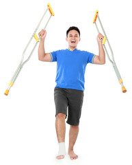 happy male with broken foot using crutch