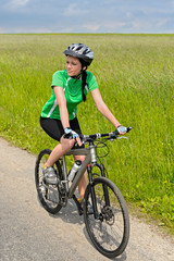 Woman biking on countryside road sunny day