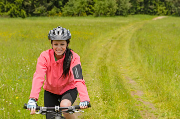 Woman riding bicycle on meadow path