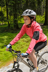 Woman mountain biking in forest motion blur