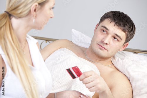 Man in bed holding credit card