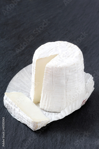 Goat cheese with a solf white mold on a black slate board
