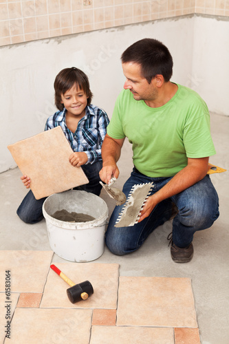 Man laying ceramic floor tiles helped by small boy