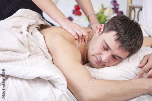 Man receiving massage on bed