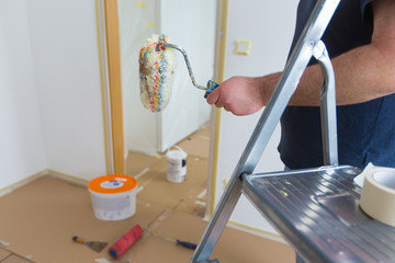 Man holding roller while renovating home