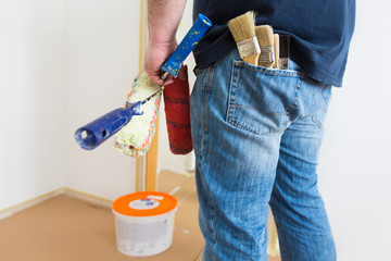 Man holding rollers and brushes while renovating home