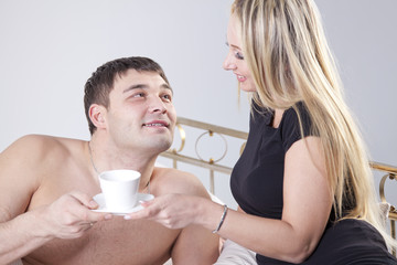 Couple drinking coffee on bed