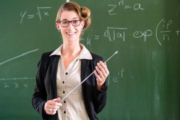 Lehrerin mit Zeigestock im Klassenzimmer in  Schule