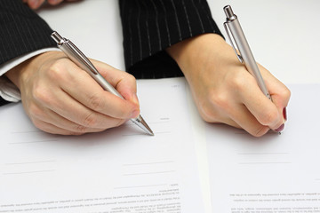 man and woman signing document or prenup