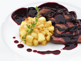 Delicious roasted sliced duck breast meat under wine and berry s