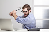 Furious businessman destroying his laptop with a hammer..