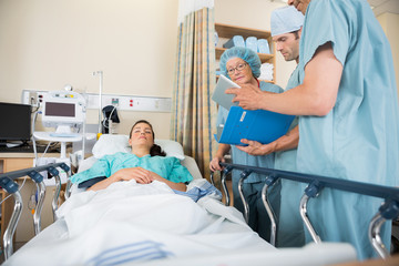 Nurses Discussing Patient's Report By Bed