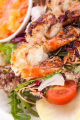 Gebratene Garnelen am Spieß auf gemischtem Salat mit Dipp und F
