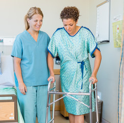 Patient Using Walker While Nurse Looking At Her