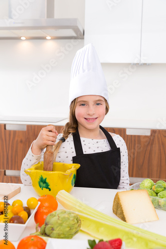 Blond kind girl junior chef on countertop