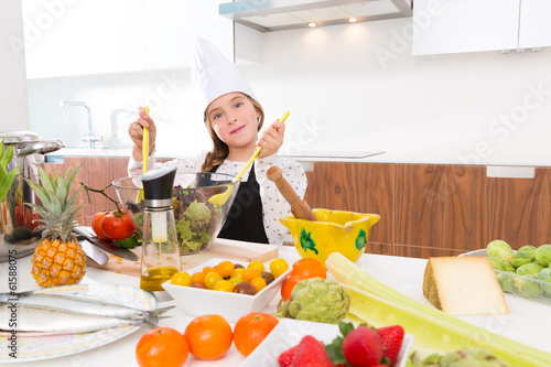 Blond kind girl junior chef on countertop salad