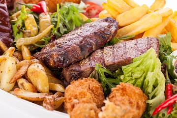Riesige Barbecueplatte mit gemischtem Fleisch und Steaks auf Sal