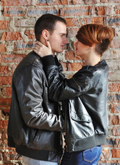 Beautiful couple in leather jackets hugging near brick wall