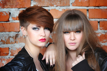 Two seductive young girls at the brick wall. Fashion portrait