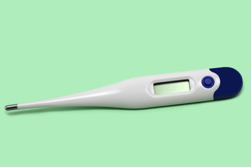 electronic medical thermometer on green background